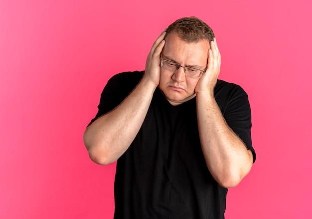 분홍색 위에 그의 머리를 만지고 슬픈 표정으로 혼란 찾고 검은 티셔츠를 입고 안경에 과체중 남자
