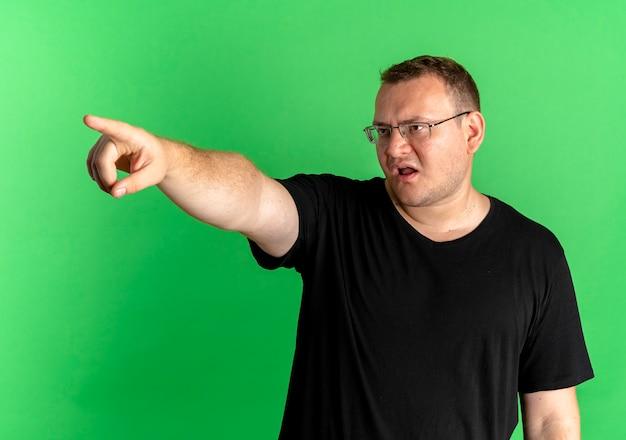 녹색 벽 위에 서있는 검지 손가락으로 comething을 가리키는 불쾌한 찾고 검은 티셔츠를 입고 안경에 과체중 남자