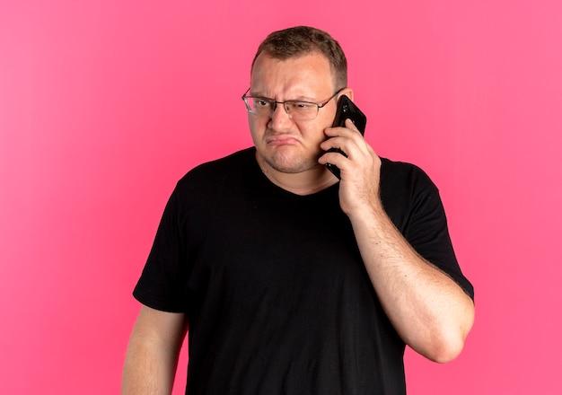 Полный мужчина в очках в черной футболке выглядит недовольным, разговаривая по мобильному телефону поверх розового