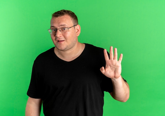 緑の壁の上に立っている手で手を振って驚いたように見える黒いtシャツを着た眼鏡の太りすぎの男