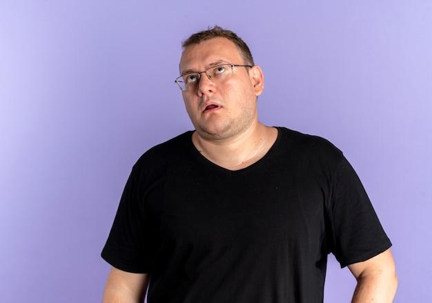 피곤하고 지루해 보이는 검은 색 티셔츠를 입고 안경에 과체중 남자가 파란색 위에 눈을 감고