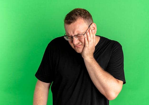 Полный мужчина в очках, одетый в черную футболку, выглядит нездоровым, трогает щеку и болит зуб над зеленой