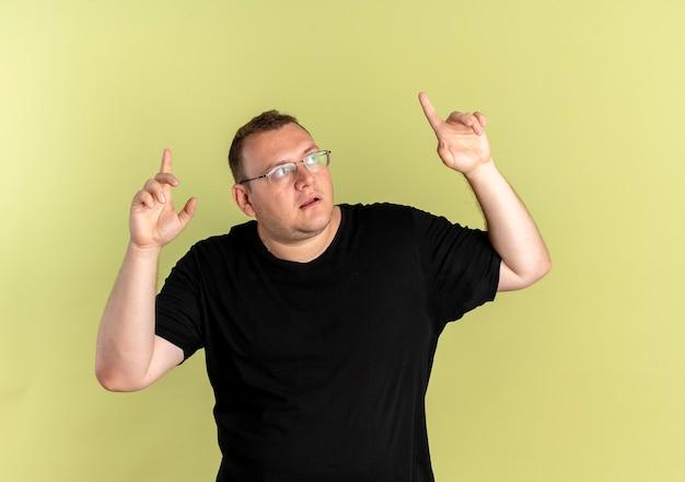 明るい壁の上に立っている人差し指で上向きに混乱して見上げる黒いtシャツを着た眼鏡の太りすぎの男