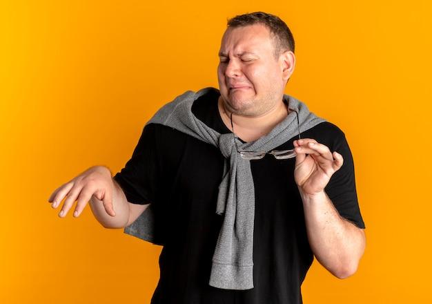 주황색 벽 위에 서있는 혐오스러운 표정으로 손으로 방어 제스처를 만드는 검은 티셔츠를 입고 안경에 과체중 남자