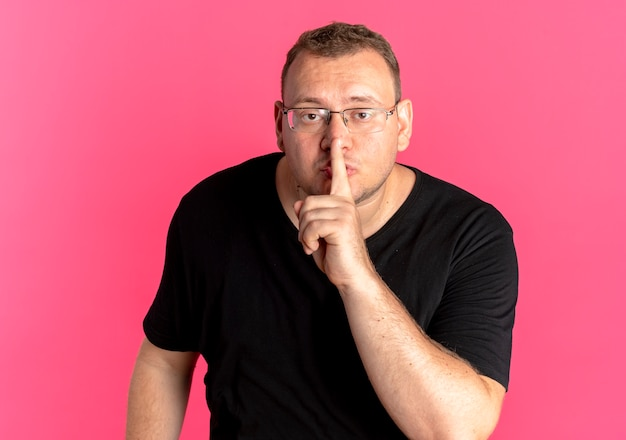 ピンクの上の唇に指で沈黙のジェスチャーをする黒いtシャツを着ている眼鏡の太りすぎの男