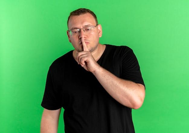 緑の壁の上に立っている唇に指で沈黙のジェスチャーをする黒いtシャツを着て眼鏡をかけた太りすぎの男