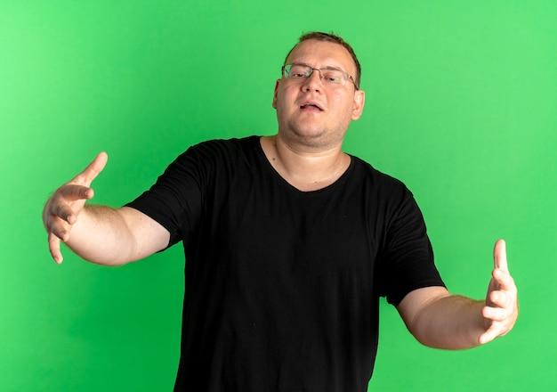 緑の壁の上に立って歓迎のジェスチャーを大きく開く手を作る黒いtシャツを着た眼鏡の太りすぎの男
