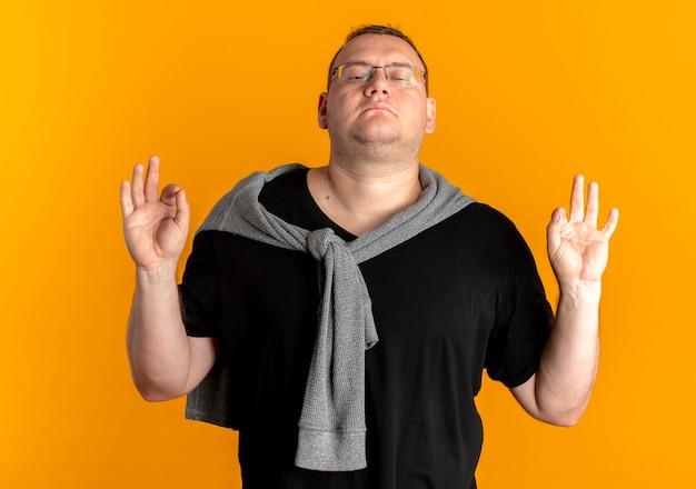 오렌지 벽 위에 서있는 손가락으로 명상 제스처를 만드는 닫힌 눈으로 편안한 검은 티셔츠를 입고 안경에 과체중 남자
