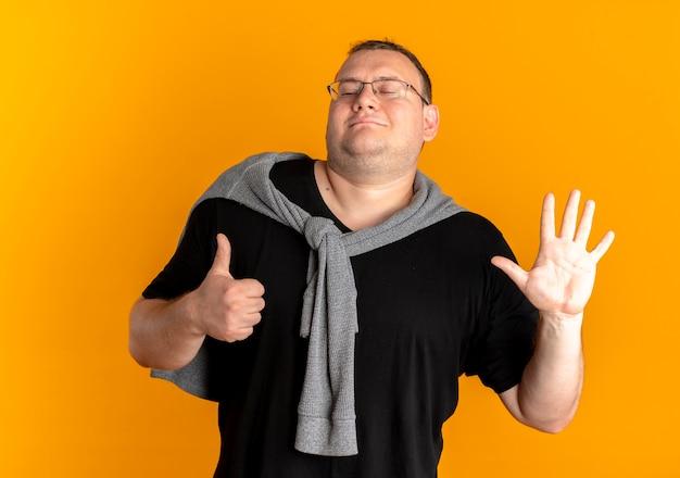 검은 색 티셔츠를 입고 주황색 벽 위에 서있는 손가락 번호 6으로 가리키는 안경에 과체중 남자
