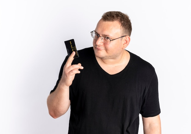 흰색 벽 위에 서 혼란 스 러 워 카메라를보고 신용 카드를 보여주는 검은 티셔츠를 입고 안경에 중량이 초과 된 남자