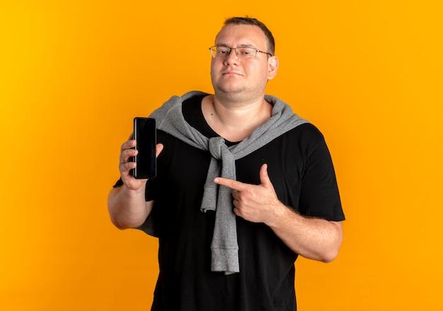 Полный мужчина в очках в черной футболке показывает смартфон, указывая пальцем на него, улыбаясь над оранжевым