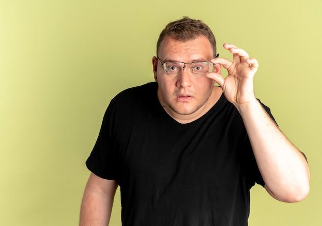 黒のtシャツを着た眼鏡の太りすぎの男性は、明るい壁の上に立っている眼鏡を固定して驚いた