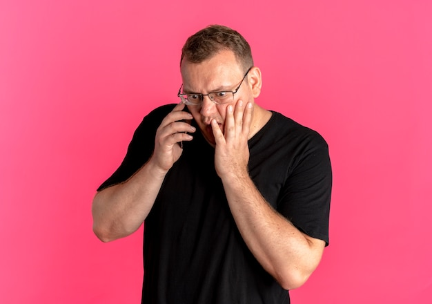 분홍색 위에 충격을 받고 휴대 전화에 얘기하는 검은 티셔츠를 입고 안경에 과체중 남자