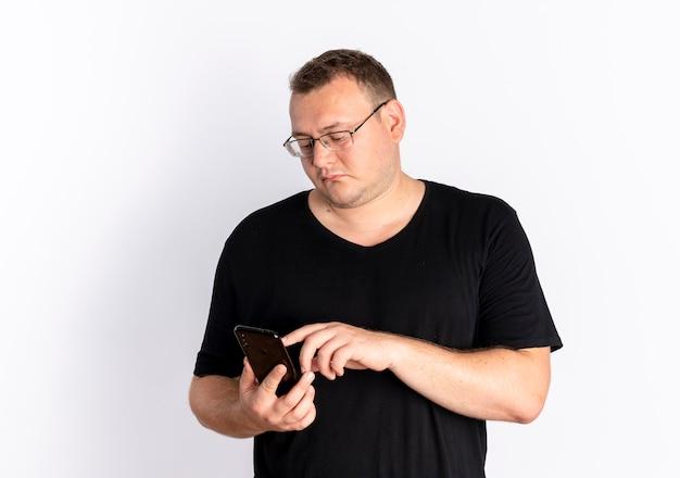 흰 벽 위에 서있는 스마트 폰을 사용하는 사람과 검은 티셔츠 문자 메시지를 쓰고 안경에 과체중 남자