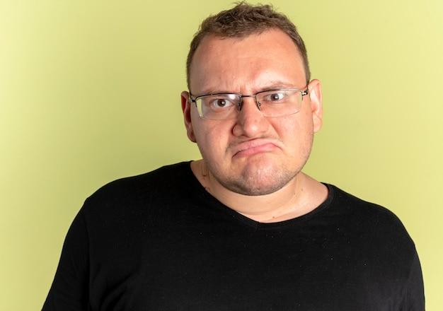 Полный мужчина в очках в черной футболке с хмурым лицом недоволен светом