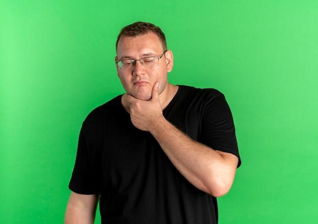 緑の壁の上に立っている顔に物思いにふける表情とあごに手で黒いtシャツを着て眼鏡をかけた太りすぎの男