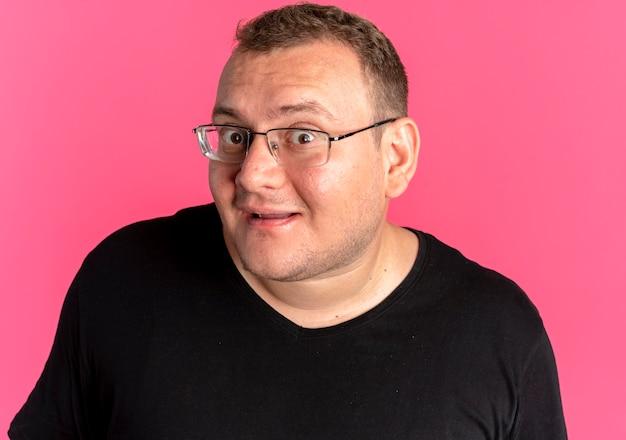 ピンクの上に微笑んで幸せそうな顔と黒のtシャツを着て眼鏡をかけて太りすぎの男