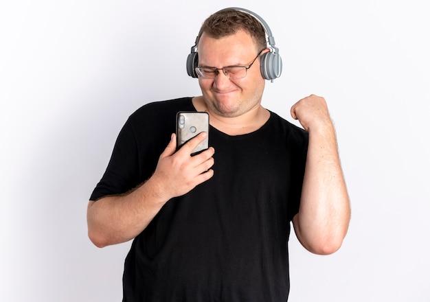 Полный мужчина в очках, одетый в черную футболку с наушниками, держит смартфон, наслаждаясь своей любимой музыкой, стоя над белой стеной