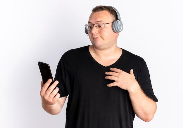 白い壁の上に立って混乱している画面を見ているスマートフォンを保持しているヘッドフォンで黒いtシャツを着て眼鏡をかけた太りすぎの男