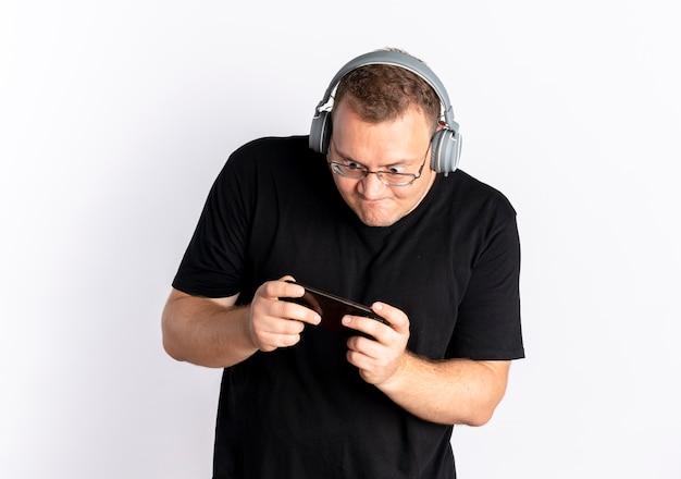 Полный мужчина в очках, одетый в черную футболку с наушниками, играет в игру на своем смартфоне, стоящем над белой стеной