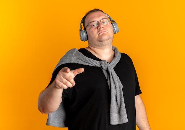 オレンジ色の壁の上に立って自信を持って見える人差し指で指しているヘッドフォンで黒いtシャツを着て眼鏡をかけた太りすぎの男