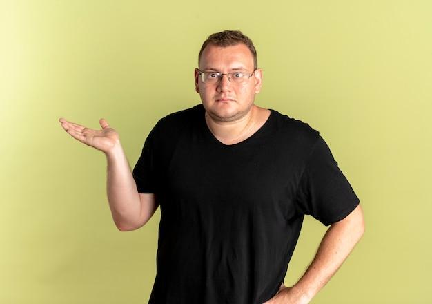 Полный мужчина в очках в черной футболке с серьезным лицом, представляя что-то с рукой, стоящей над светлой стеной