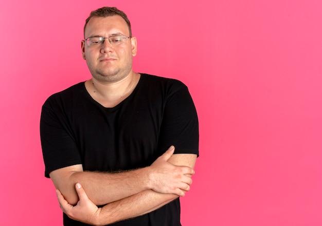 ピンクの壁の上に立っている胸に腕を組んで顔に笑顔で黒いtシャツを着て眼鏡をかけた太りすぎの男