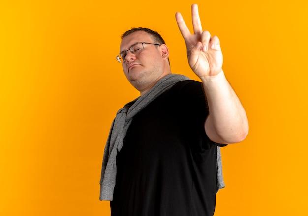 オレンジ色の壁の上に立っている勝利のサインを示す自信を持って見える黒いtシャツを着て眼鏡をかけた太りすぎの男