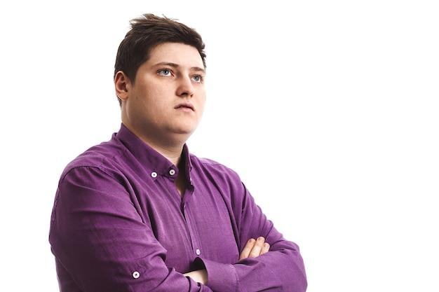 Полный мужчина в фиолетовом задумчиво стоит на белом