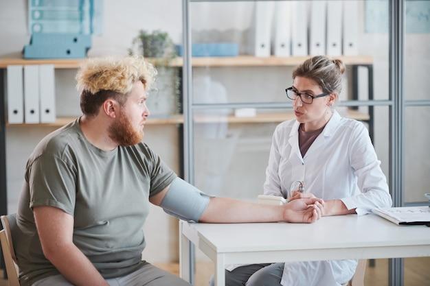 Полный мужчина сидит за столом и разговаривает с врачом, пока она измеряет ему давление во время ...