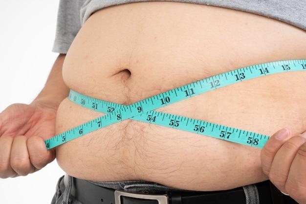 과체중 남자는 자신의 뚱뚱한 배를 측정하기 위해 측정 테이프를 사용합니다