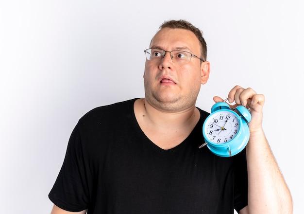 白い壁の上に立って混乱して目をそらしている目覚まし時計を保持している眼鏡で黒いtシャツを着ている太りすぎの男
