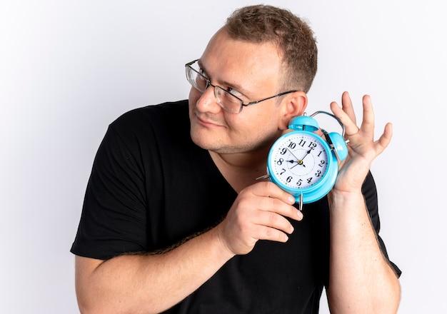 흰색 벽 위에 서있는 소리를 듣고 그의 귀 근처에 알람 시계를 들고 안경에 검은 색 티셔츠를 입고 과체중 남자
