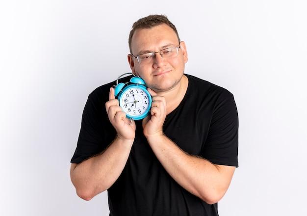 흰 벽 위에 서있는 긍정적 인 감정을 느끼는 행복한 얼굴로 알람 시계를 들고 안경에 검은 색 티셔츠를 입은 과체중 남자