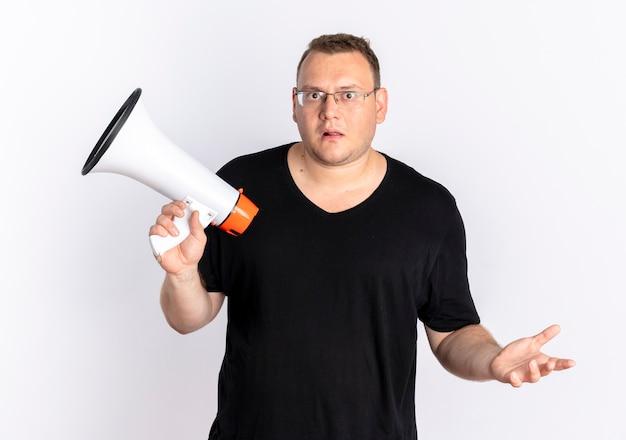 확성기를 들고 안경에 검은 티셔츠를 입고 과체중 남자가 흰 벽 위에 서서 혼란스럽고 불쾌한 모습을 보입니다.