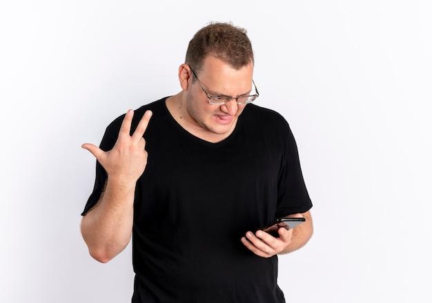그의 스마트 폰 화면을보고 안경에 검은 티셔츠를 입고 과체중 남자가 혼란스럽고 흰 벽 위에 서있는 손으로 몸짓을 불쾌하게 함