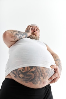 Overweight man with big belly and tattoos in sports wear is holding his stomach with shocked emotion