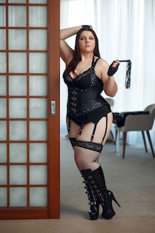 Overweight perverse woman in erotic lingerie holding leather whip.