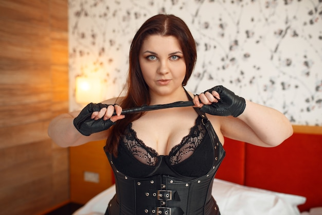 Overweight perverse woman in erotic lingerie holding a whip.