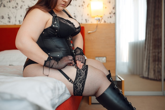 Overweight perverse woman puts on erotic lingerie sitting on the bed.