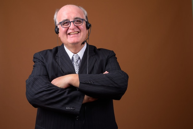 Overweight senior businessman wearing eyeglasses against brown wall