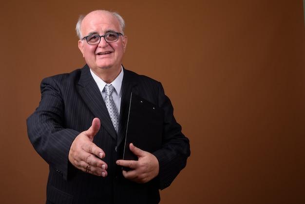 Старший бизнесмен с избыточным весом в очках на коричневой стене