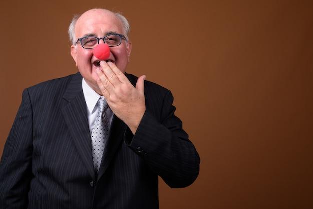 Старший бизнесмен с избыточным весом, носящий красный клоунский нос