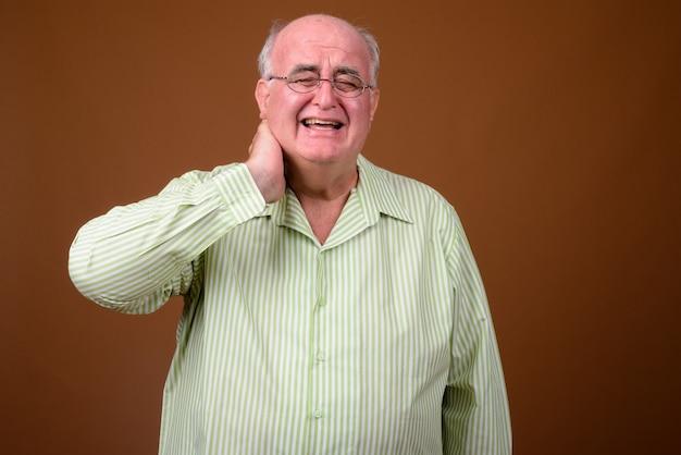 Overweight senior man wearing eyeglasses against brown wall