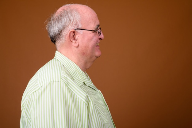 Overweight senior man wearing eyeglasses against brown wall