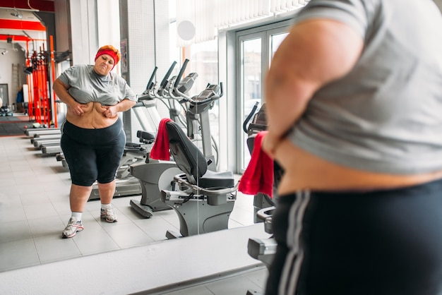 Overweight sweaty woman watches on her body against mirror in gym. calories burning, obese female person in sport club
