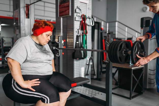 Overweight sweaty woman on workout with barbell in gym. calories burning, obese female person in sport club