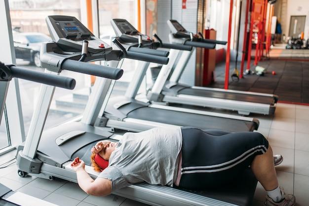 Усталая женщина с избыточным весом лежит на беговой дорожке в тренажерном зале