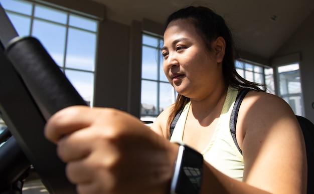 Полная женщина делает фитнес-тренировку на велосипеде в тренажерном зале. концепции здорового образа жизни и спорта.