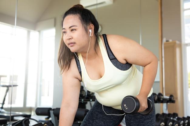 Полная женщина делает фитнес-тренировку с весами в тренажерном зале. здоровый образ жизни и спортивные концепции.